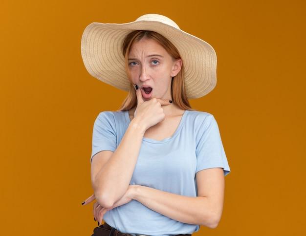 Zweifelhaftes junges rothaariges ingwermädchen mit sommersprossen, die strandhut tragen, hält kinn und schaut kamera auf orange