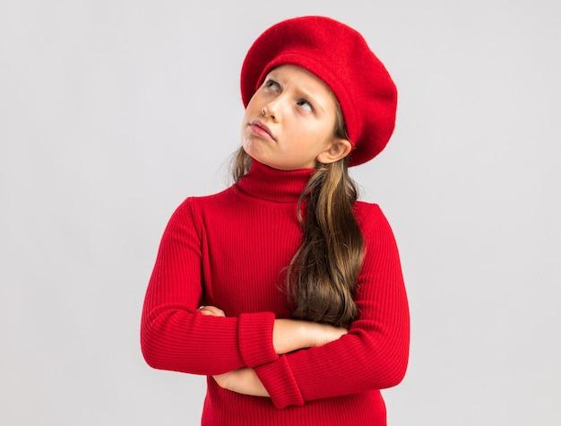 Zweifelhaftes kleines blondes mädchen mit rotem barett, das die arme verschränkt hält und nach oben isoliert auf weißer wand mit kopierraum schaut
