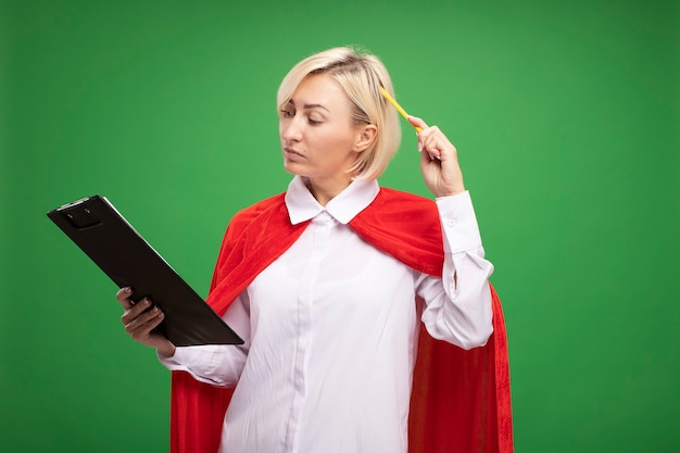 Zweifelnde blonde superheldin mittleren alters im roten umhang, die die zwischenablage hält und betrachtet und den kopf mit bleistift berührt