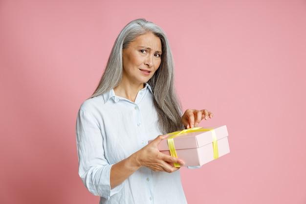 Zweifelnde grauhaarige asiatin öffnet eine geschenkbox, die mit seidenband verziert ist und auf rosafarbenem hintergrund im studio posiert