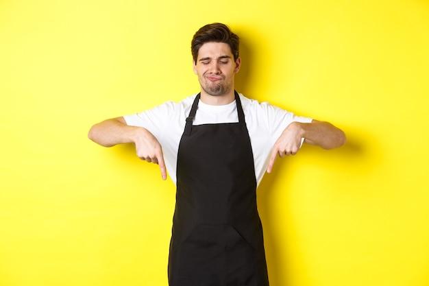 Zweifelnder barista beschwert sich, zeigt mit den fingern nach unten und verzieht unzufrieden das gesicht, in schwarzer schürze vor gelbem hintergrund stehend