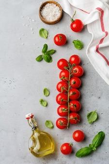 Zweig der rohen frischen kirschtomaten, des olivenöls und des basilikums der blätter auf grau