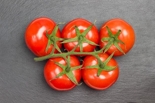 Zweig der tomate auf schwarzem hintergrund. flach liegen