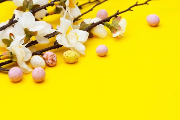 Zweig der weißen blumen auf gelbem hintergrund mit süßigkeit, osterschokolade ärgert. ostern verspotten. minimalistic frühlingshintergrund.