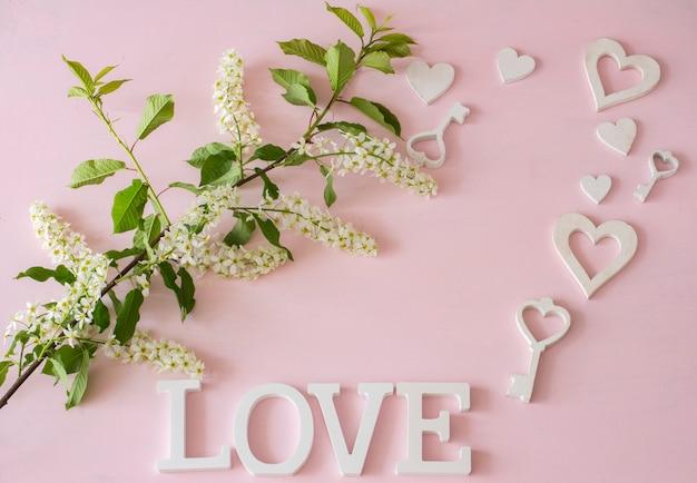 Zweig der weißen vogelkirsche, herzen, schlüssel auf einem rosa hintergrund
