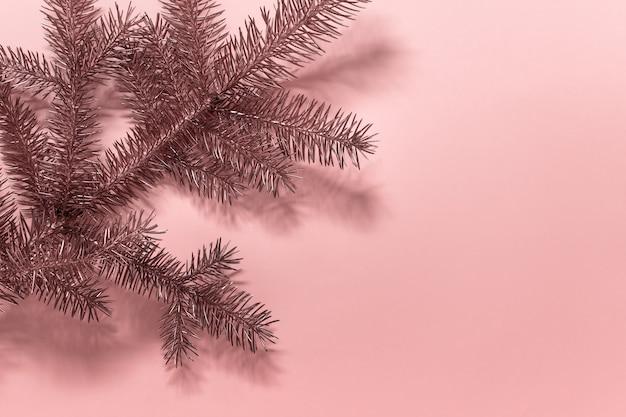 Zweig des immergrünen weihnachtsbaums, der mit goldener farbe auf rosa oberfläche gefärbt wird.