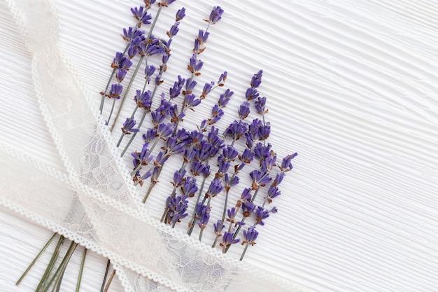 Zweig des lavendels auf hölzerner struktureller oberfläche mit band.