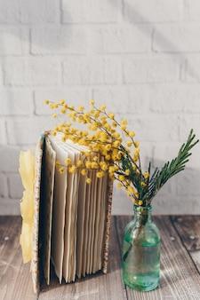 Zweig gelber mimosenblüten in einer kleinen flasche mit einem notizbuch