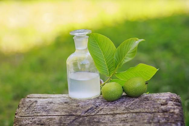 Zweig mit zwei unreifen grünen walnüssen mit blättern zur herstellung von medikamenten und tinkturen. klare flasche mit elixierkorken. flasche medizin