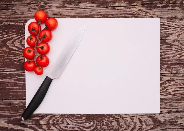 Zweig von kirschtomaten mit scharfem messer auf weißem leerem papier über dem hölzernen schreibtisch