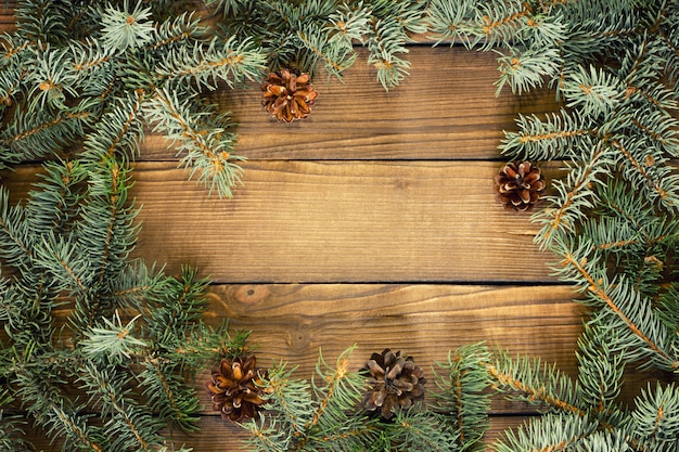 Zweige der fichte auf einem hölzernen hintergrund, weihnachtshintergrund