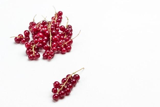 Zweige der roten johannisbeeren auf weiß. beerenhintergrund. ansicht von oben. platz kopieren