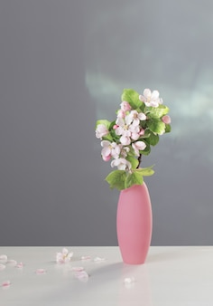 Zweige des apfelbaums mit blumen in der rosa vase auf weißem tisch
