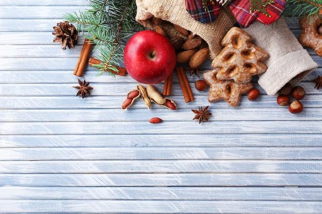 Zweige des weihnachtsbaums mit keksen, apfel und gewürzen auf farbigem holzhintergrund