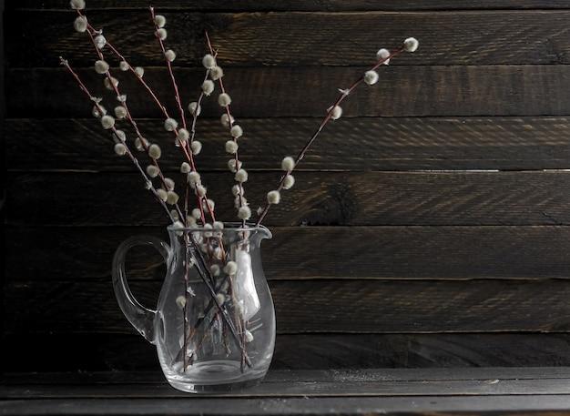 Zweige einer blühenden weide stehen in einem dunklen glas vor einem hintergrund