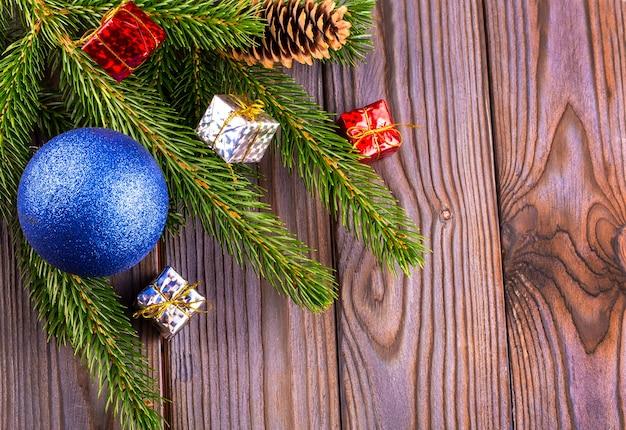 Zweige eines mit blauer kugel geschmückten weihnachtsbaums und spielzeug mit seide auf einem holztisch