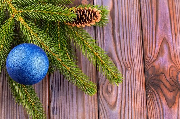 Zweige eines mit blauer kugel mit seide geschmückten weihnachtsbaums auf einem holztisch
