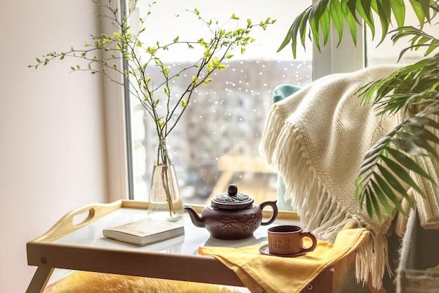 Zweige in der flasche auf dem couchtisch mit plaid, buch, teekanne und einer tasse mit einer verregneten stadt außerhalb des fensters (im hintergrund). konzept eines gefühls der gemütlichkeit zu hause.