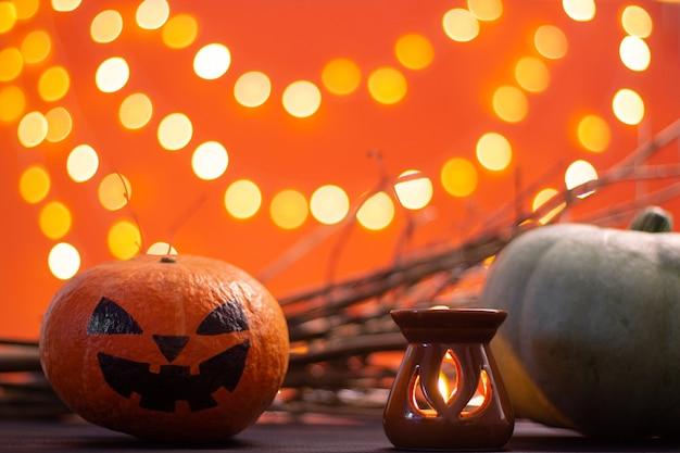 Zweige, kerzen und kürbisse auf orangefarbenem hintergrund mit bokeh. halloween. platz kopieren.
