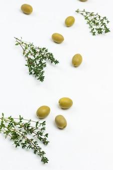 Zweige thymian und oliven auf dem tisch. flach liegen.