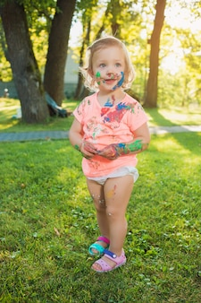 Zweijähriges mädchen in farben gegen grünen rasen befleckt