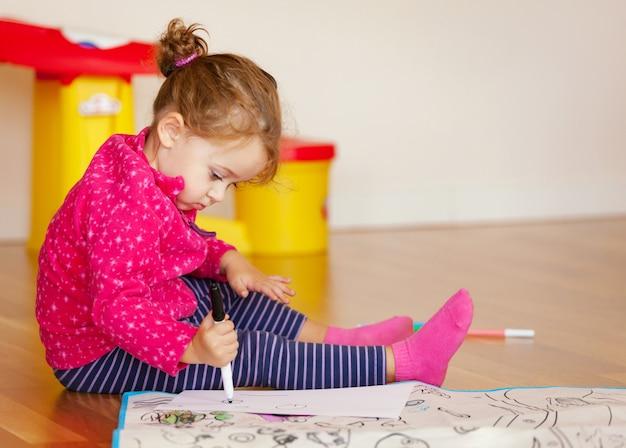 Zweijähriges mädchen zeichnet und farben auf dem fußboden.