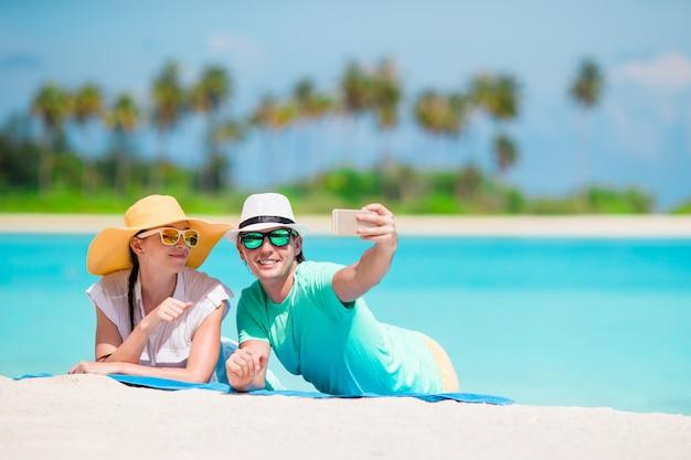 Zweiköpfige familie, die ein selfie mit mobiltelefon auf strand macht