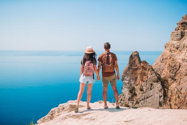 Zweiköpfige familie reist in die berge. konzept der touristen auf der klippe