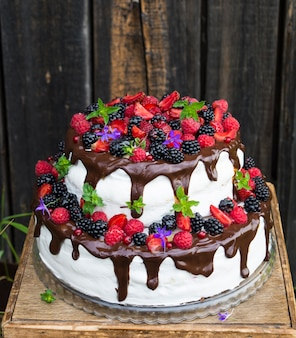 Zweistöckiger kuchen mit früchten und blumen. dessert. schwarzwälder kirschtorte