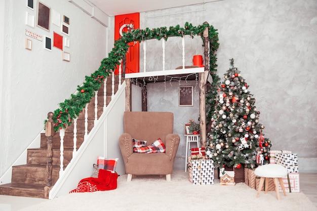 Zweistöckiges zimmer im klassischen neujahrsstil mit großem stuhl und weihnachtsbaum