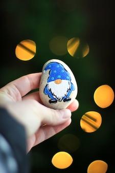 Zwerg auf einem stein. steinspielzeug in der hand auf einem weihnachtshintergrund. lichter im hintergrund