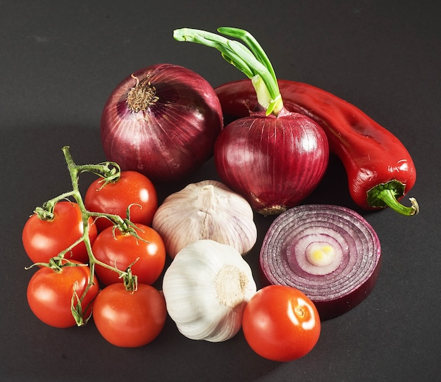Zwiebel und knoblauch und peperoni und tomaten isoliert auf einem schwarzen.