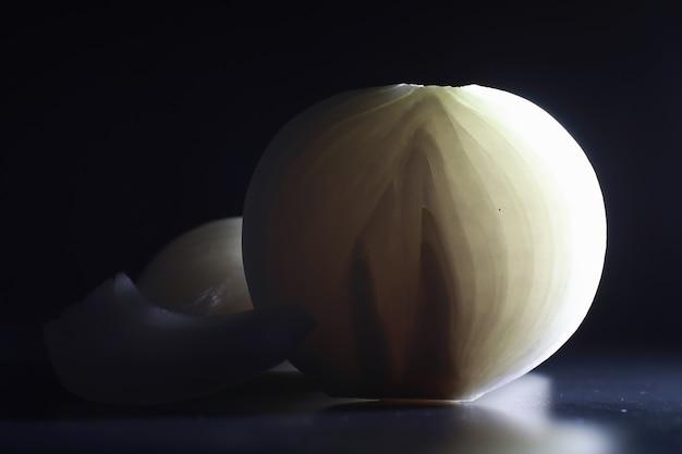 Zwiebeln der frischen zwiebel auf schwarzem hintergrund. zwiebelzwiebel ist reich an vitaminen, nützlicher frühling. zwiebelschale auf dunklem hintergrund. rohe geschnittene zwiebeln.