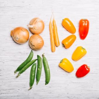 Zwiebeln und erbsen in der nähe von karotten und paprika