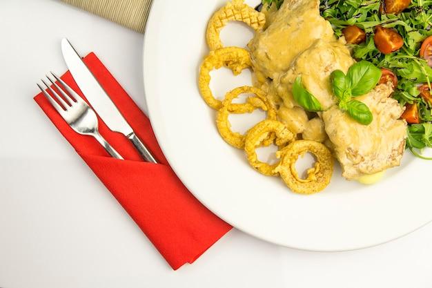 Zwiebelringe, huhn in senfhonigsauce, gnocchi und rucola auf weißem teller mit besteck