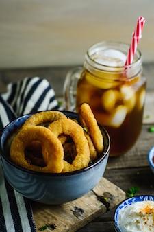Zwiebelringe, sauce und soda in einem holztisch