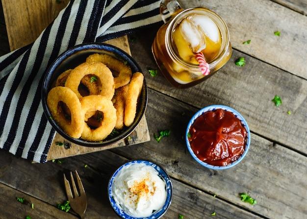 Zwiebelringe, saucen und soda in einem holztisch