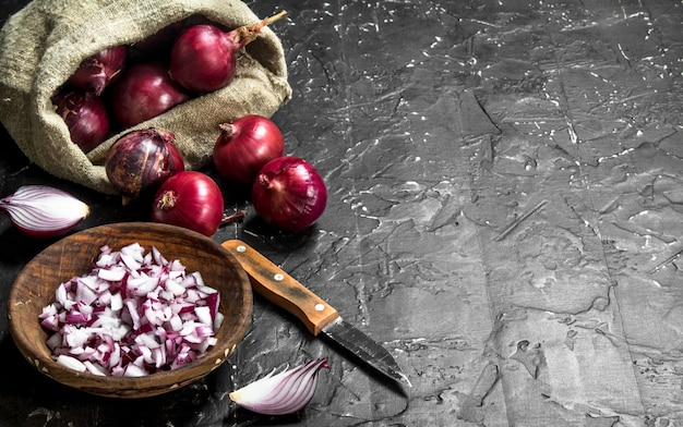 Zwiebelstücke in einer schüssel und zwiebeln im sack mit einem messer. auf schwarzem rustikalem hintergrund