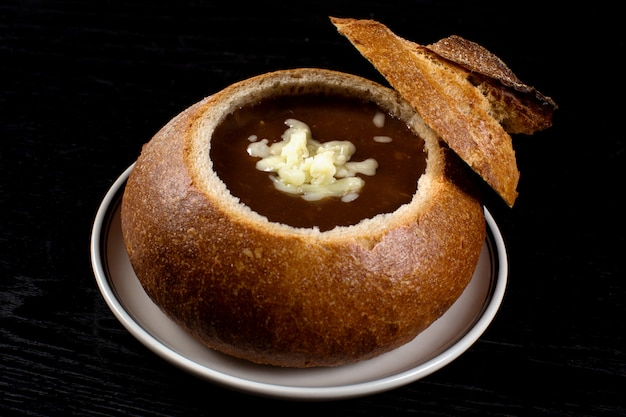 Zwiebelsuppe im schwarzbrot mit geriebenem käse