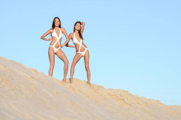 Zwillinge am strand tragen modische strandkleidung. zwei perfekt geformte zwillinge der jungen frau, die sich am meer sonnen.