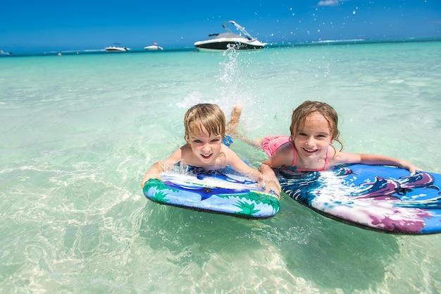 Zwillinge bruder und schwester, um spaß beim surfen im meer zu haben