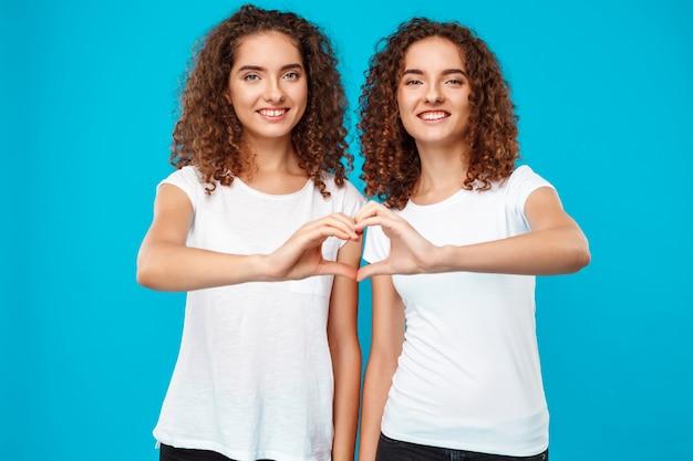 Zwillinge der frau, die herz mit den händen über blau zeigen.