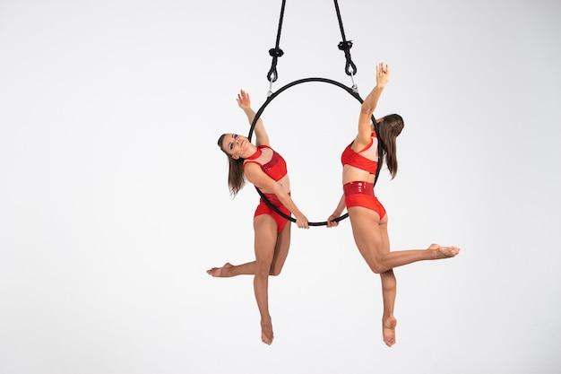 Zwillinge weibliches zirkusduo auf dem luftreifen isoliert auf weiß