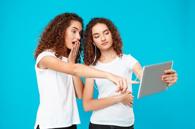 Zwillinge zweier frauen, die tablette betrachten, überrascht über blau.