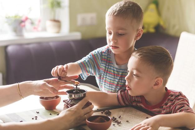 Zwillingsbrüder, die ihrer mutter helfen, kaffee zu mahlen