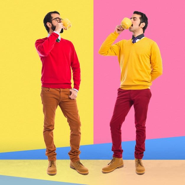 Zwillingsbrüder halten tasse kaffee
