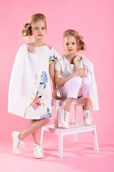 Zwillingsmädchen in der hellen kleidung, die nahe der treppe mit zwei schritten auf einem rosa aufwirft