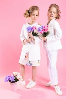 Zwillingsmädchen in leichter kleidung mit blumensträußen stehen auf rosa.
