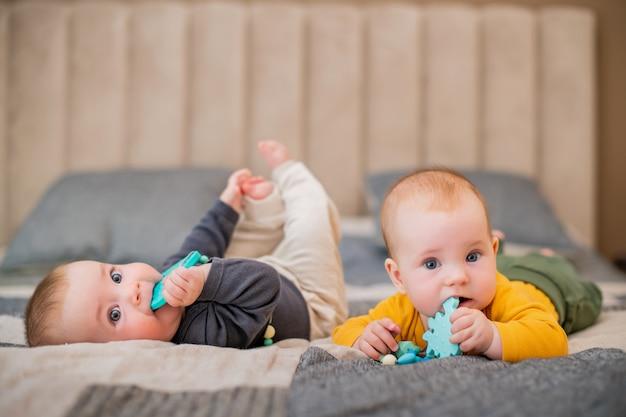 Zwillingsmädchenbabys liegen auf dem bett und nagen an beißringen