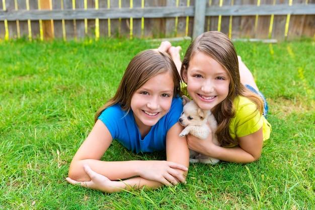 Zwillingsschwesterkindmädchen und welpenhund liegend im rasen